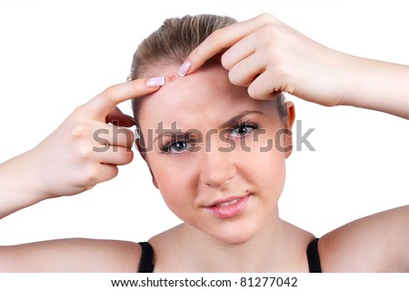 Teenager problem skin care - woman squeeze pimple on white background - stock photo