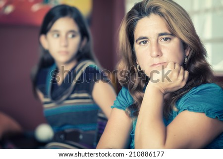 Teenager problems - Sad and worried mother with her rebellious teenage daughter on the background - stock photo
