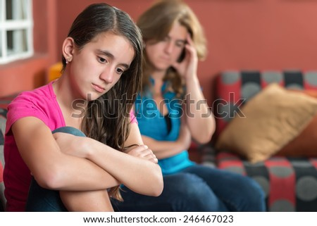 Teenager problems - Sad teenage girl and her worried mother - stock photo