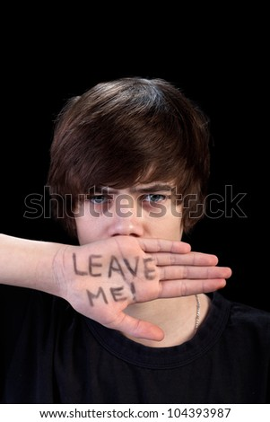 Teenager refusing help looking angry - on black background - stock photo