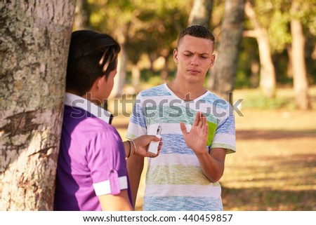 Teenager refusing to smoke electronic cigarette. Concept of health and social issues between young people.  - stock photo