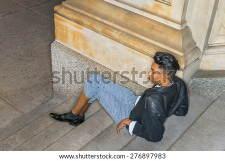 Teenager relaxing on stairs.  A young dark skin,18 years old student, wearing black fashionable leather, wool mixed jacket, striped pants, leather shoes, short hair, sitting back on stairs, relaxing.  - stock photo