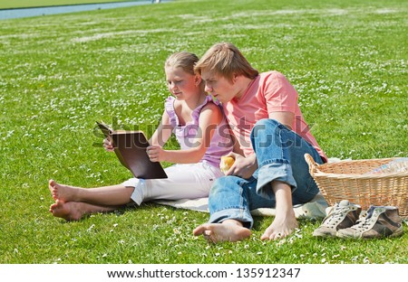 Teenager siblings reading book at picnic in the park in a bright sunny day - stock photo