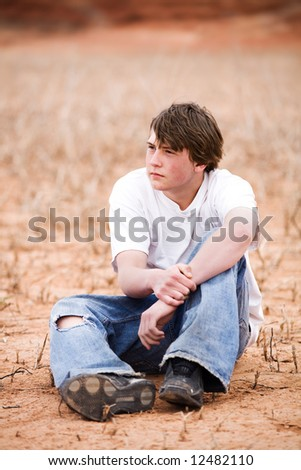 teenager sitting amongst the weeds in a dry lake bed. Natural-looking teen, simple clothing, ripped jeans, shot in Wyoming with copyspace. - stock photo