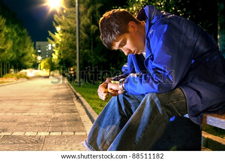 teenager sitting in the night park alley and looking on the watch - stock photo