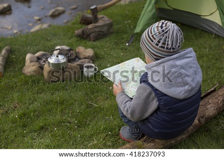 Teenager sitting near the fire and looking at the map. - stock photo