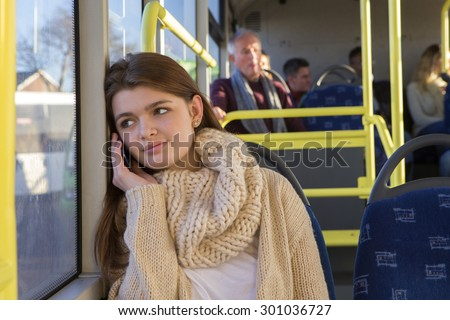 Teenager sitting on the bus. She is looking out the window and is on the phone to someone.  - stock photo