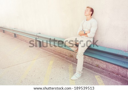 Teenager sitting with closed eyes outdoors - stock photo
