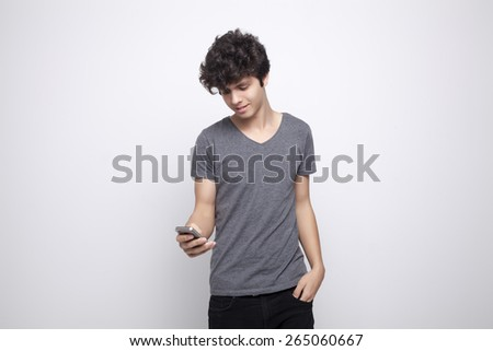 Teenager smiling and holding a smart phone - stock photo