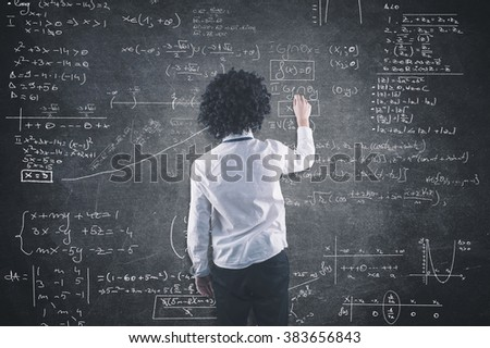 Teenager solving a math equation on blackboard - stock photo