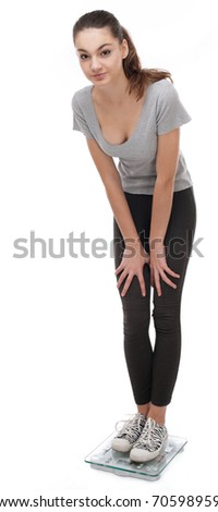 Teenager standing on scales. Isolated on a white background. - stock photo