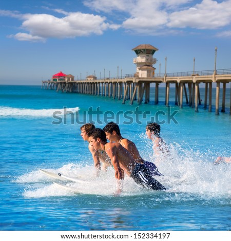 Teenager surfers surfing running jumping on surfboards at Huntington beach pier California [ photo-illustration] - stock photo
