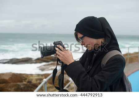 Teenager taking photos with his camera near the sea.  - stock photo
