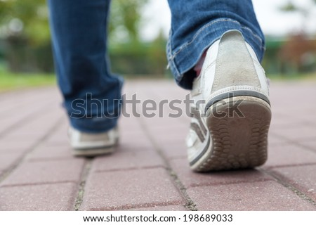 Teenager walking in sport shoes on pavement at summer day - stock photo
