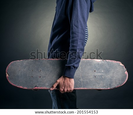 teenager with a skateboard in hand - stock photo