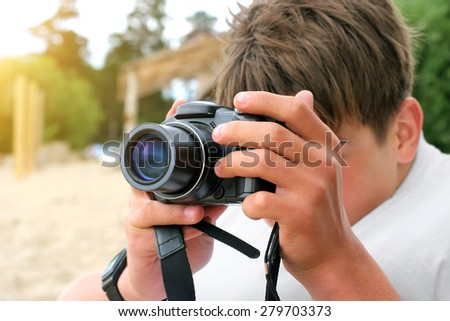 teenager with digital photo camera aiming outdoor - stock photo