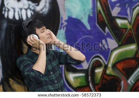 Teenager with headphones listening to music - stock photo