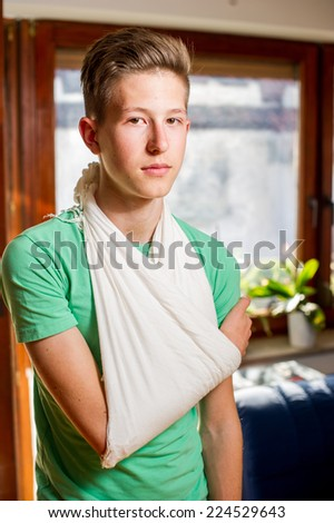 Teenager with his arm in a sling. - stock photo