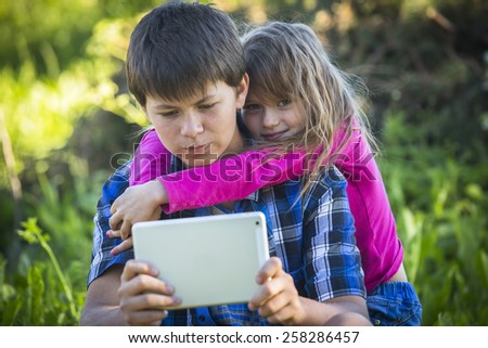 Teenager with his younger sister sitting outdoors and using the tablet. - stock photo
