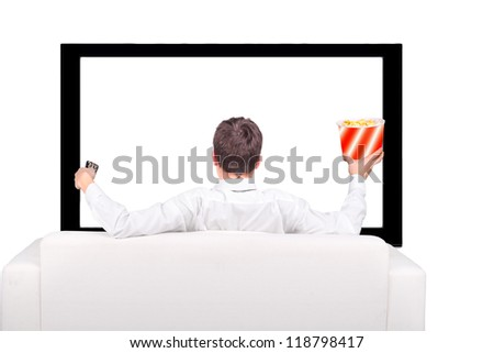 Teenager with Remote Control and Popcorn sitting on the Sofa and watching Tv-set - stock photo