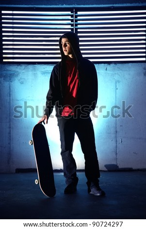 teenager with skateboard at night blue background - stock photo
