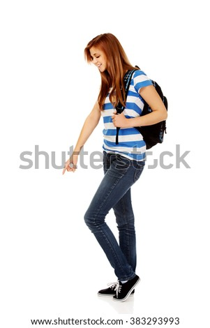 Teenager woman with backpack pointing for soomething - stock photo