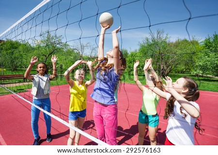 Teenagers are playing volleyball on the court - stock photo