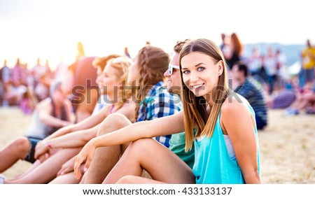Teenagers at summer music festival, sitting on the ground - stock photo