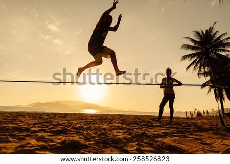 teenagers balance jumping on slackline with risk on sunrise beach silhouette - stock photo