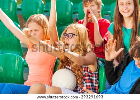 Teenagers cheer for team during game at stadium - stock photo