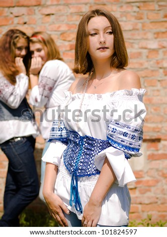 Teenagers gossiping over brick wall background or portrait of three beautiful young women with communication issue - stock photo