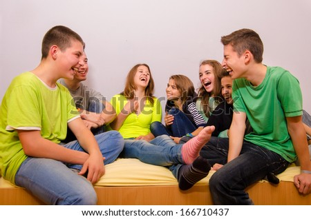 Teenagers having fun at home while sitting on bed. - stock photo