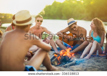 Teenagers having fun at the beach. They are sitting in the sand in circle around a camp fire, wearing short pants, sunglasses and straw hats. They are singing and a boy is playing guitar - stock photo