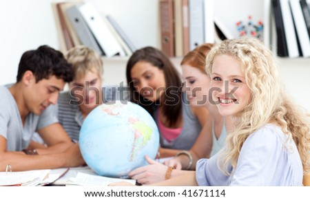 Teenagers in a library working with a terrestrial globe and taking notes - stock photo