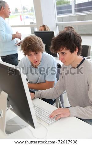 Teenagers in classroom working on desktop computer - stock photo