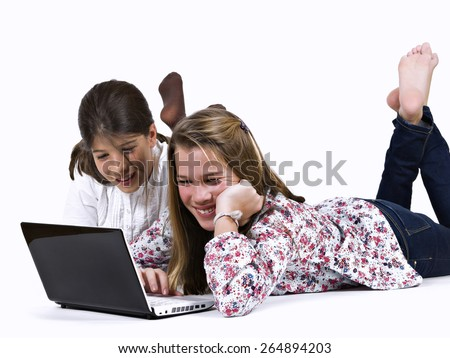Teenagers in the soil, playing with a portable computer - stock photo