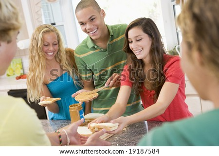 Teenagers Making Peanut Butter Sandwiches - stock photo