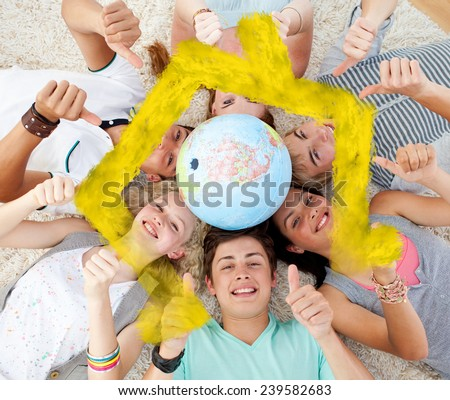 Teenagers on the floor with a terrestrial globe in the center and with thumbs up against house outline in clouds - stock photo