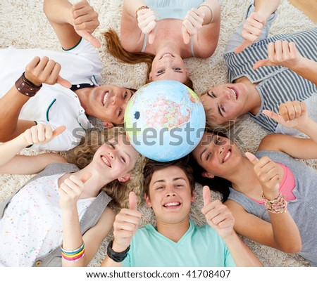 Teenagers on the floor with a terrestrial globe in the center of their heads and with thumbs up - stock photo