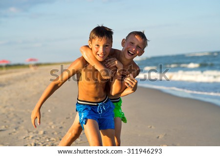 Teenagers playing on the sea beach at summer. - stock photo