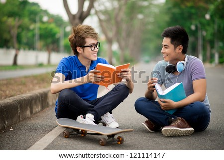 Teenagers reading books outdoors in the park - stock photo
