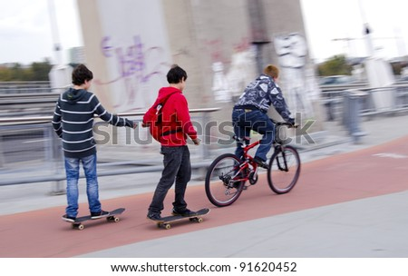 Teenagers riding bikes and skateboards on urban bicycle trail. - stock photo