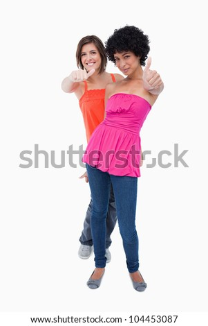 Teenagers showing thumbs up one behind the other against a white background - stock photo