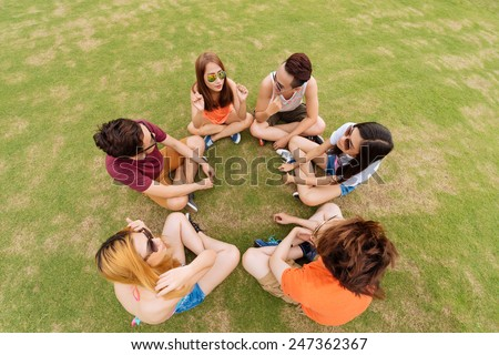 Teenagers sitting on the ground and talking with each other, view from above - stock photo
