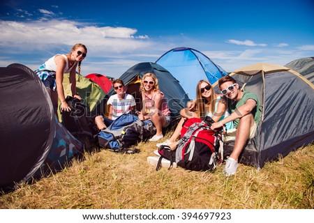 Teenagers sitting on the ground in front of tents - stock photo