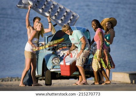 Teenagers standing beside car near water, carrying cool box and inflatable, smiling - stock photo