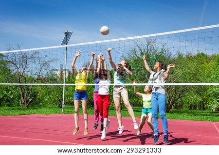 Teenagers team actively playing volleyball game - stock photo