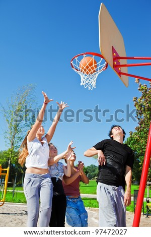 Teenagers throwing ball to the basketball hoop - stock photo