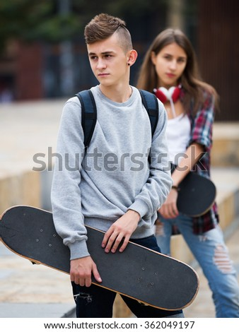 Teenagers with skateboards having a city walk in sunny day  - stock photo