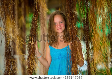 Teengirl in a blue dress in mangrove forest. - stock photo